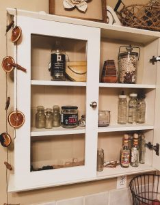My cabinet where I showcase all the empty jars I save so I can repurpose them with various different items.