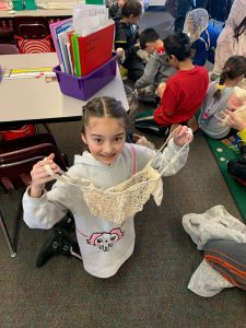 3rd grade girl holding up her UnEARTH Netted Bag to the camera!